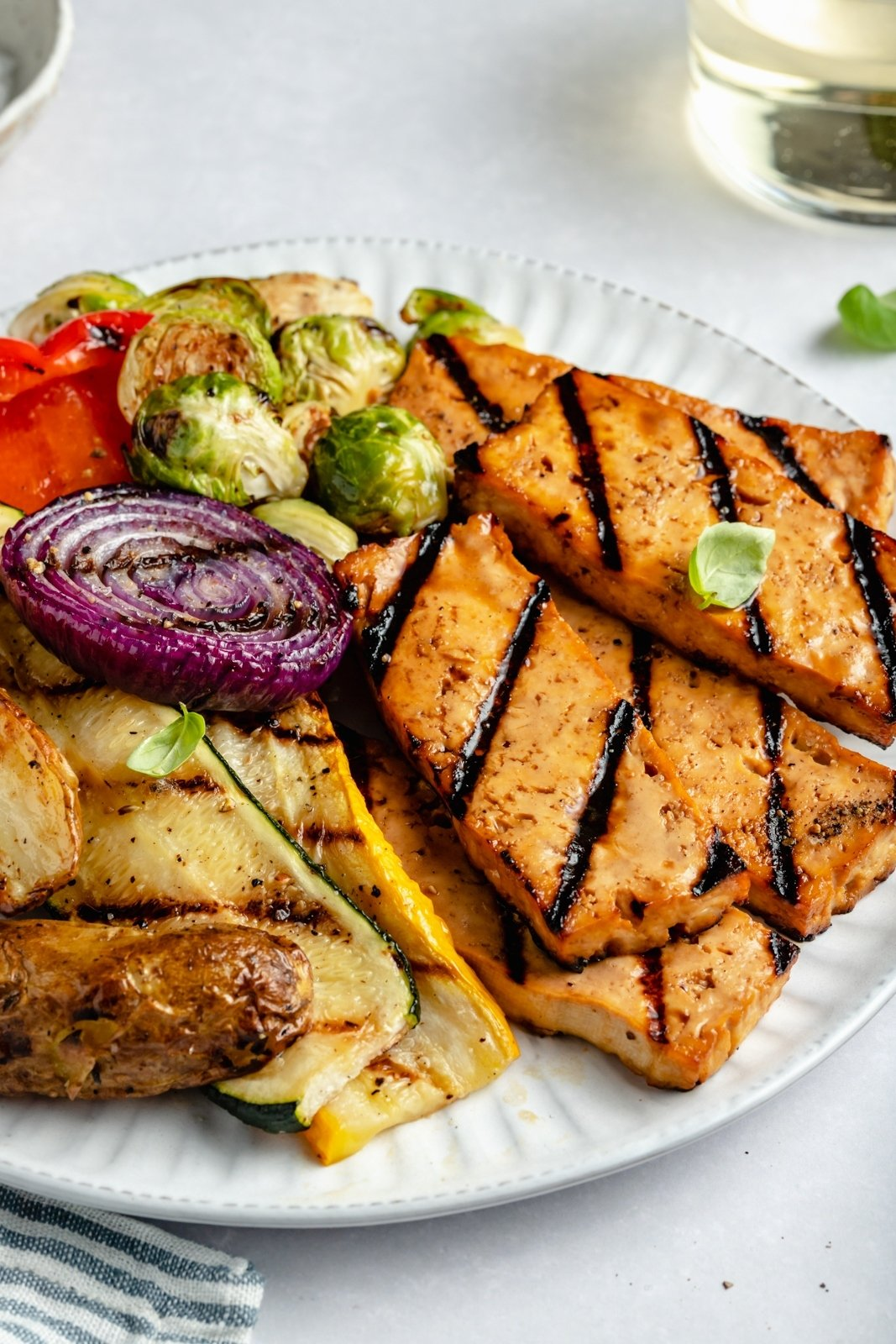 grilled tofu on a plate with grilled vegetables