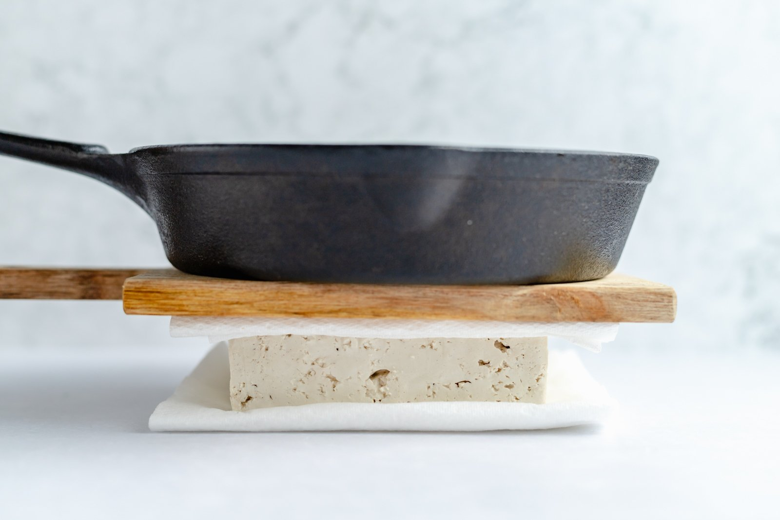 pressing tofu with a wooden board and a cast iron skillet