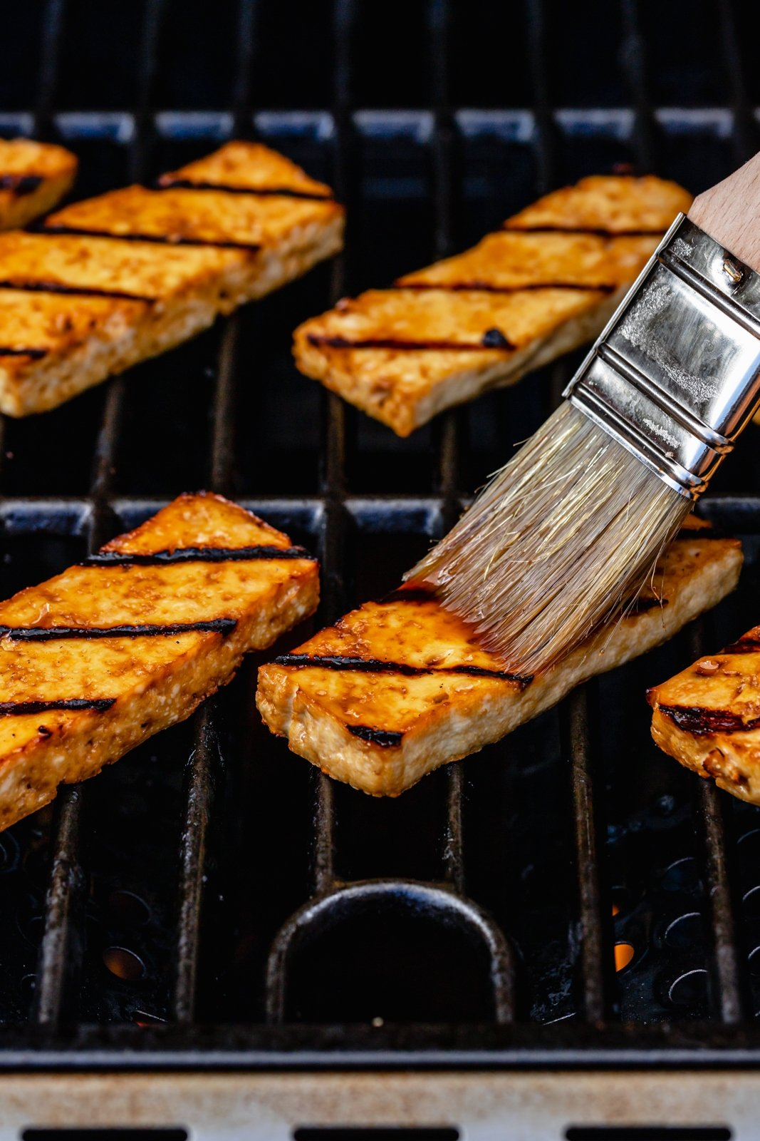 brushing grilled tofu with a marinade