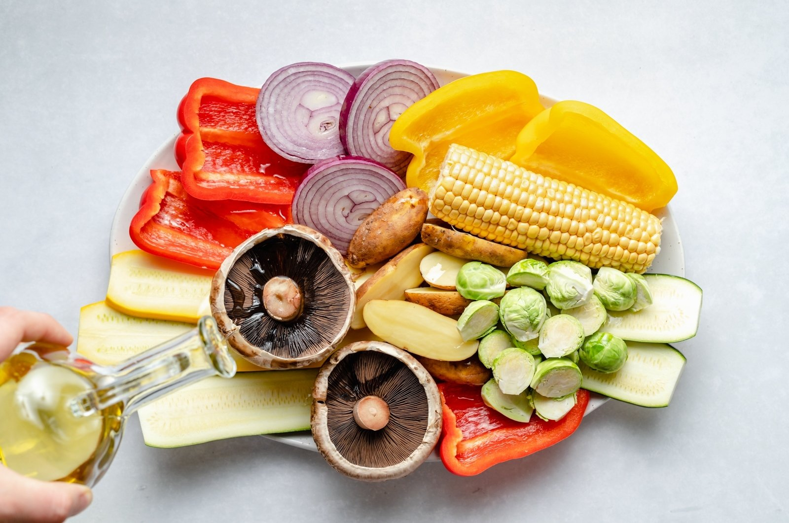drizzling a platter of vegetables with olive oil