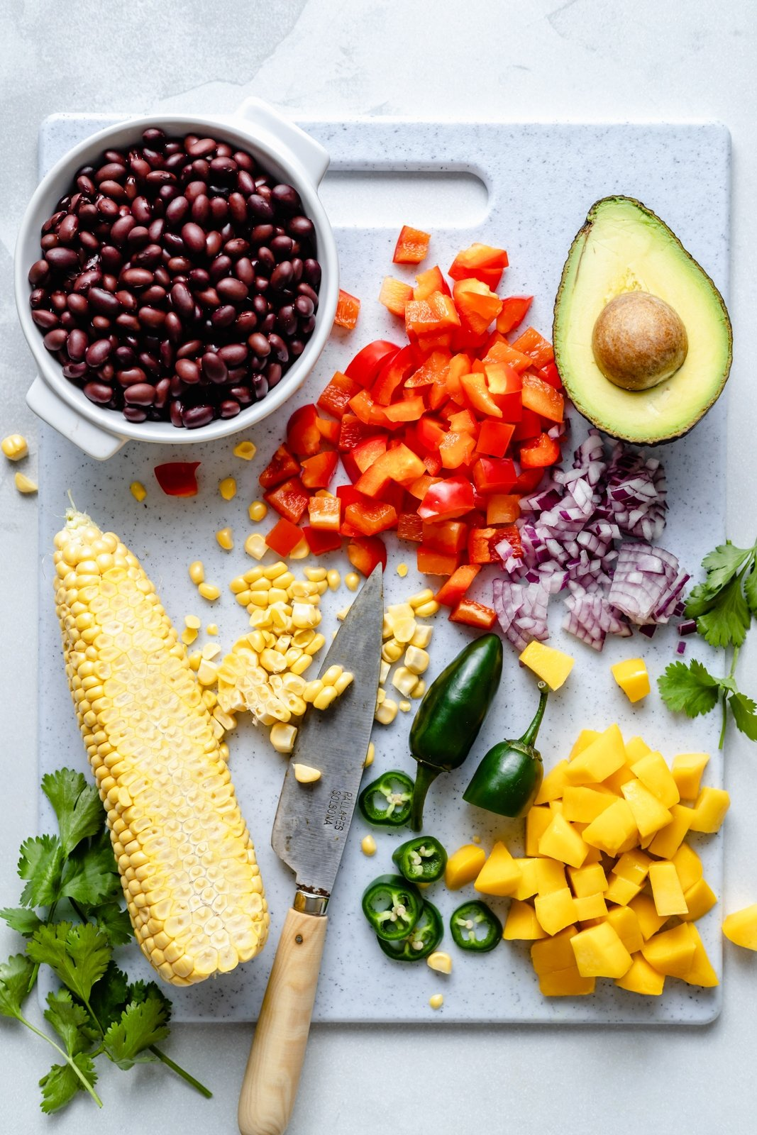 ingredients for a green rice burrito bowl on a cutting board