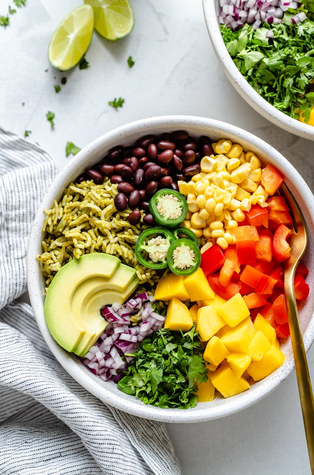 green rice bowl with mango, avocado, corn, bell pepper and black beans