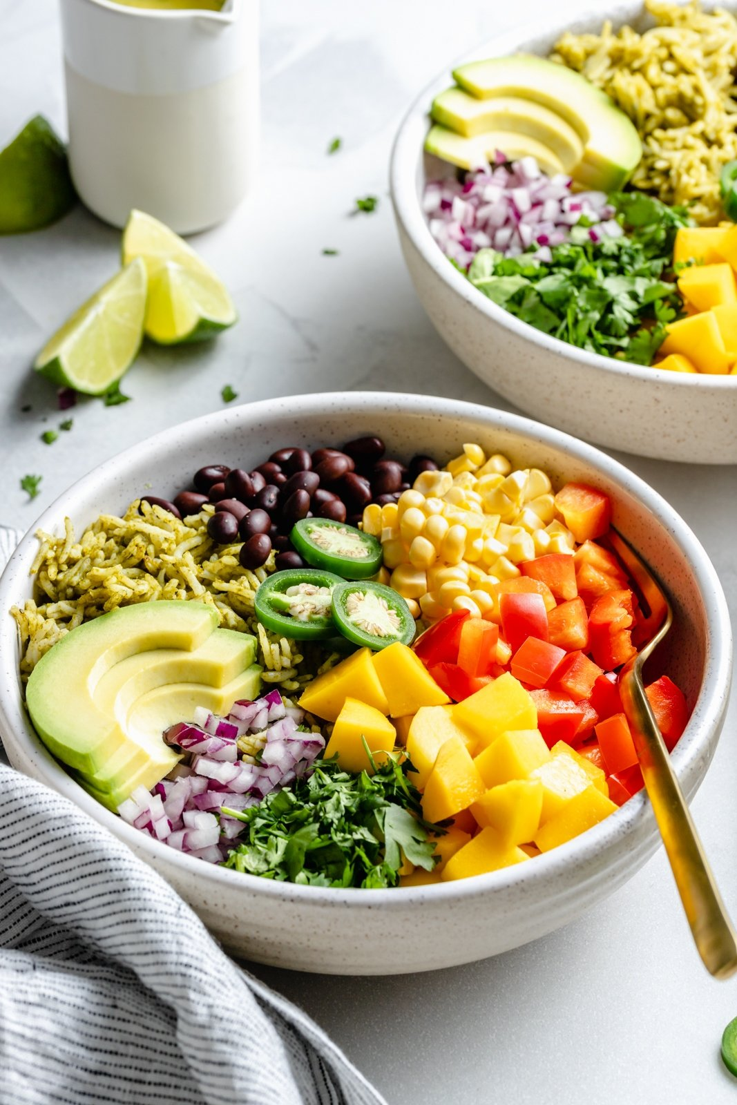 vegetarian green rice bowls topped with veggies and mango