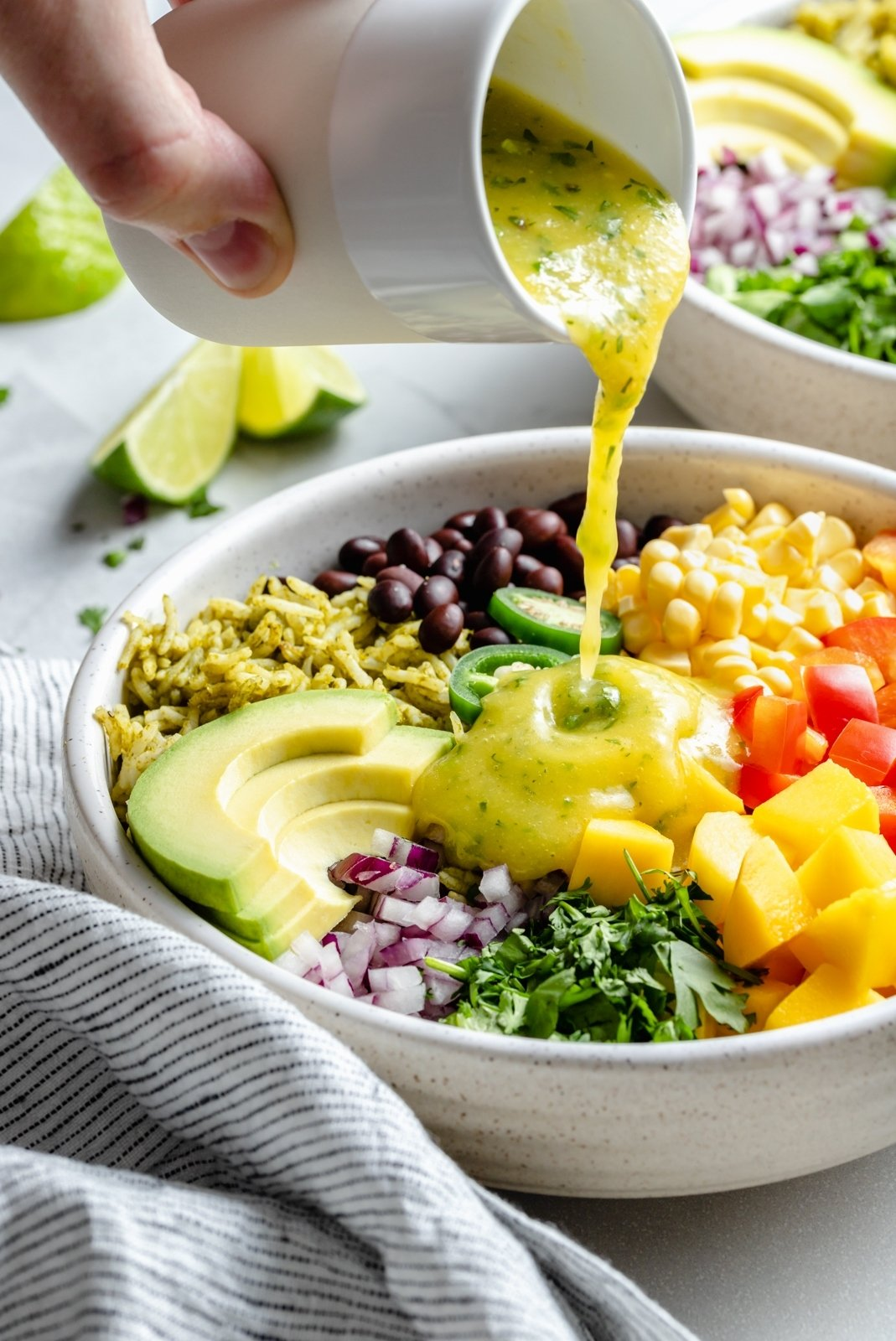 pouring dressing onto a green rice burrito bowl
