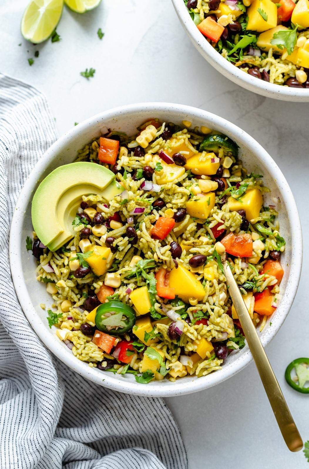 vegan green rice bowl with avocado, mango and black beans