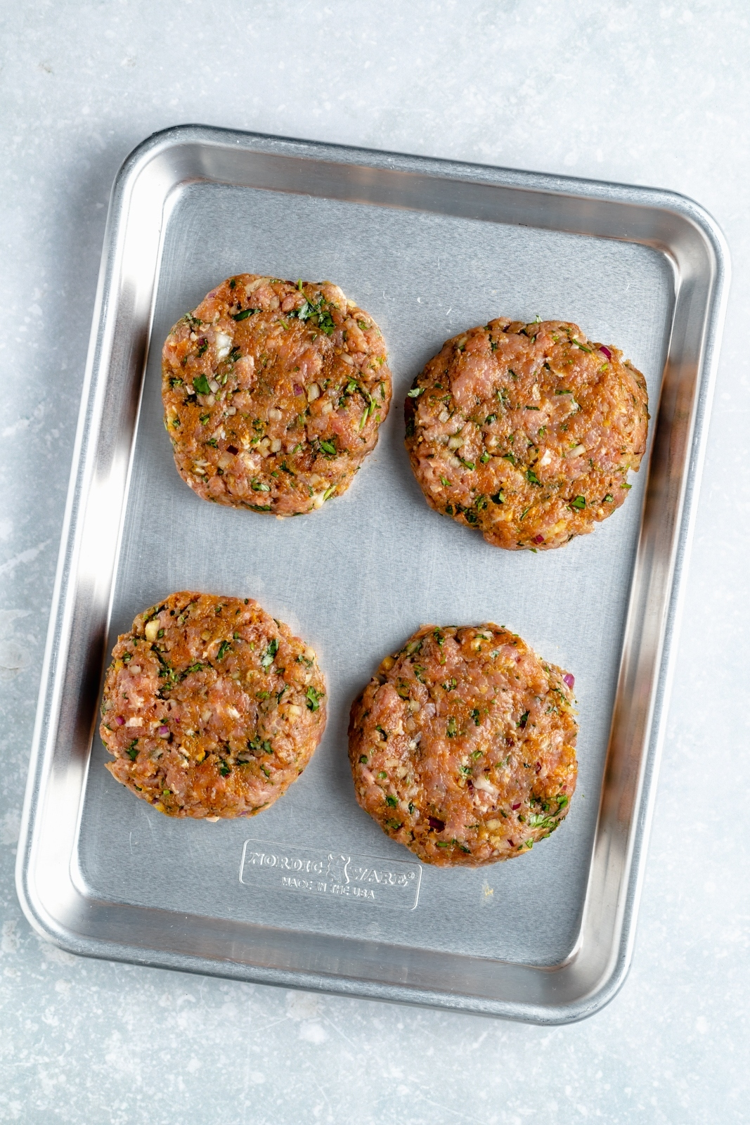 moroccan turkey burgers on a baking sheet before grilling