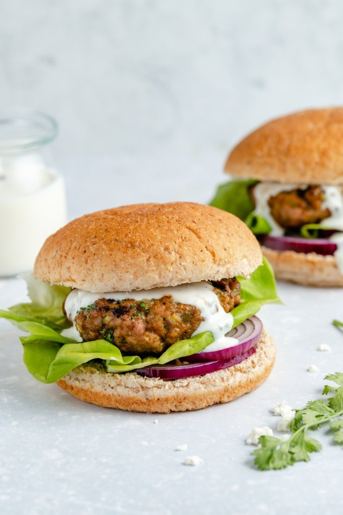 moroccan-inspired turkey burger topped with feta sauce, lettuce and red onion