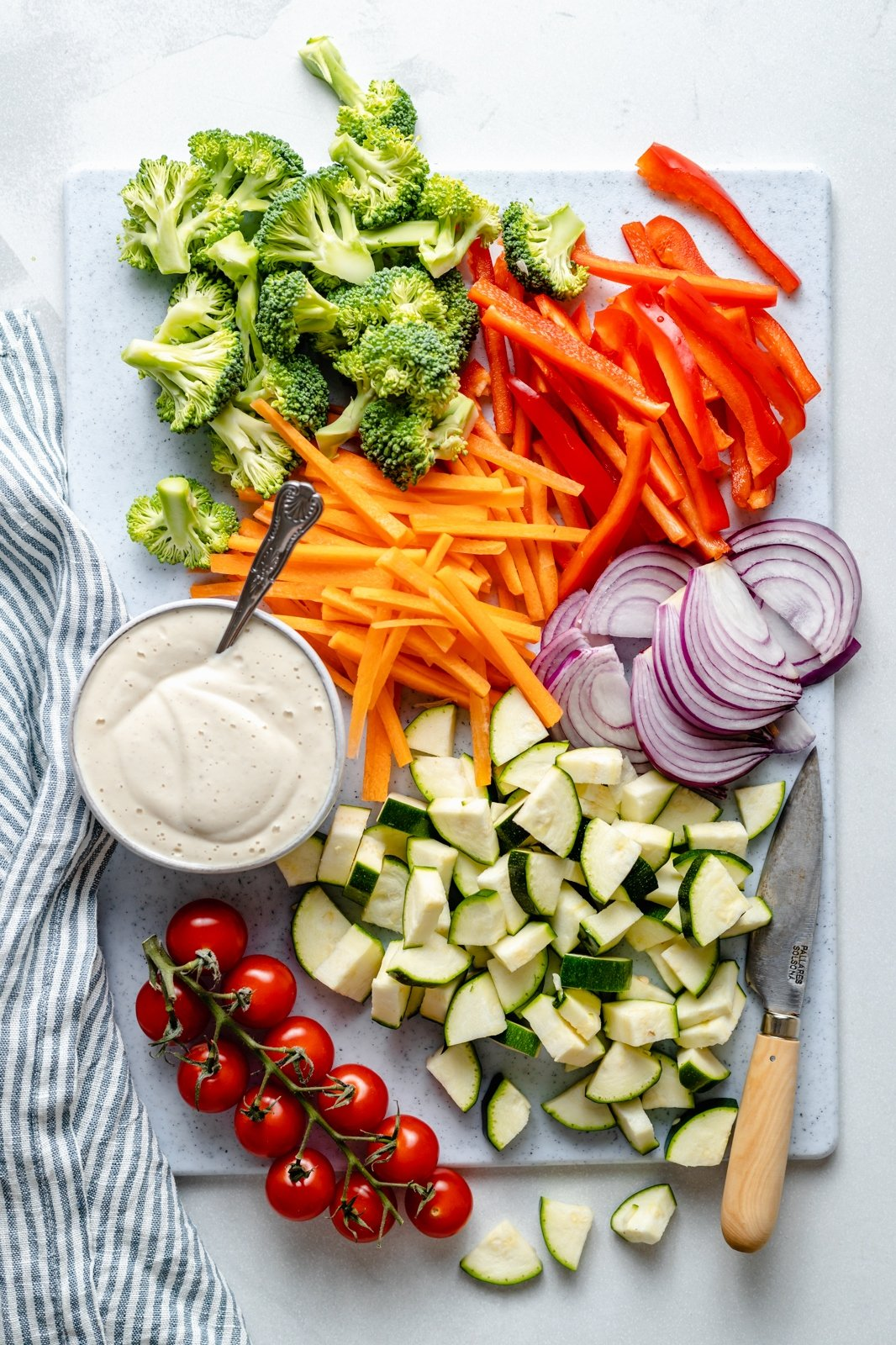 vegetables and sauce laid out on a board to make vegan pasta primavera