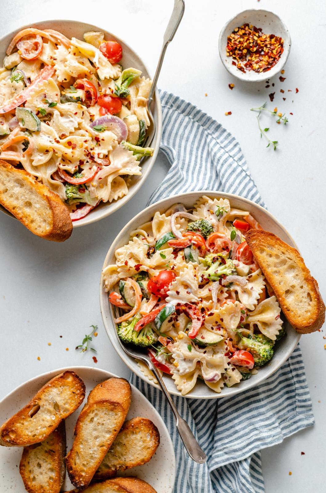 the best vegan pasta primavera in two bowls with garlic bread