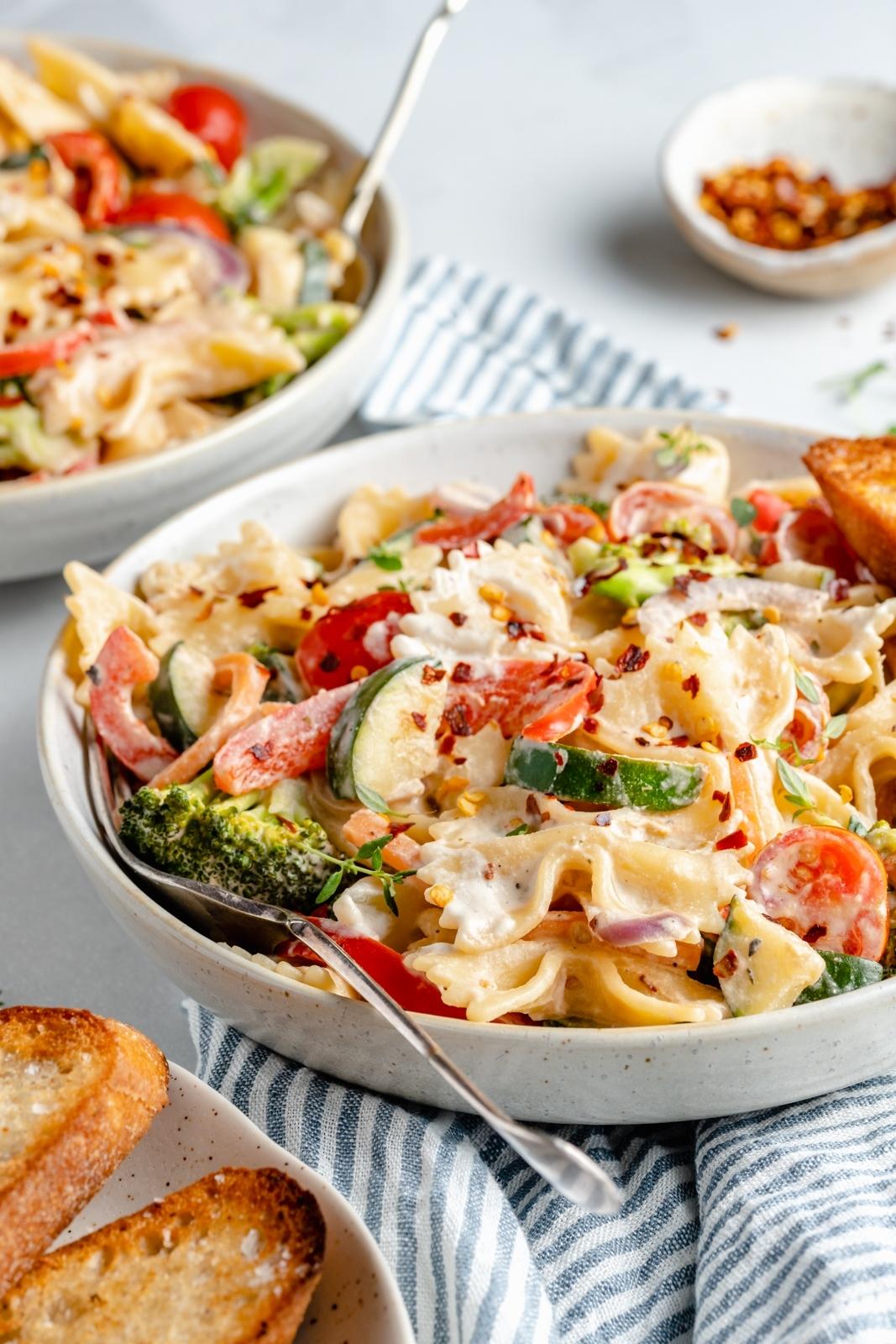 vegan pasta primavera in a bowl with a fork