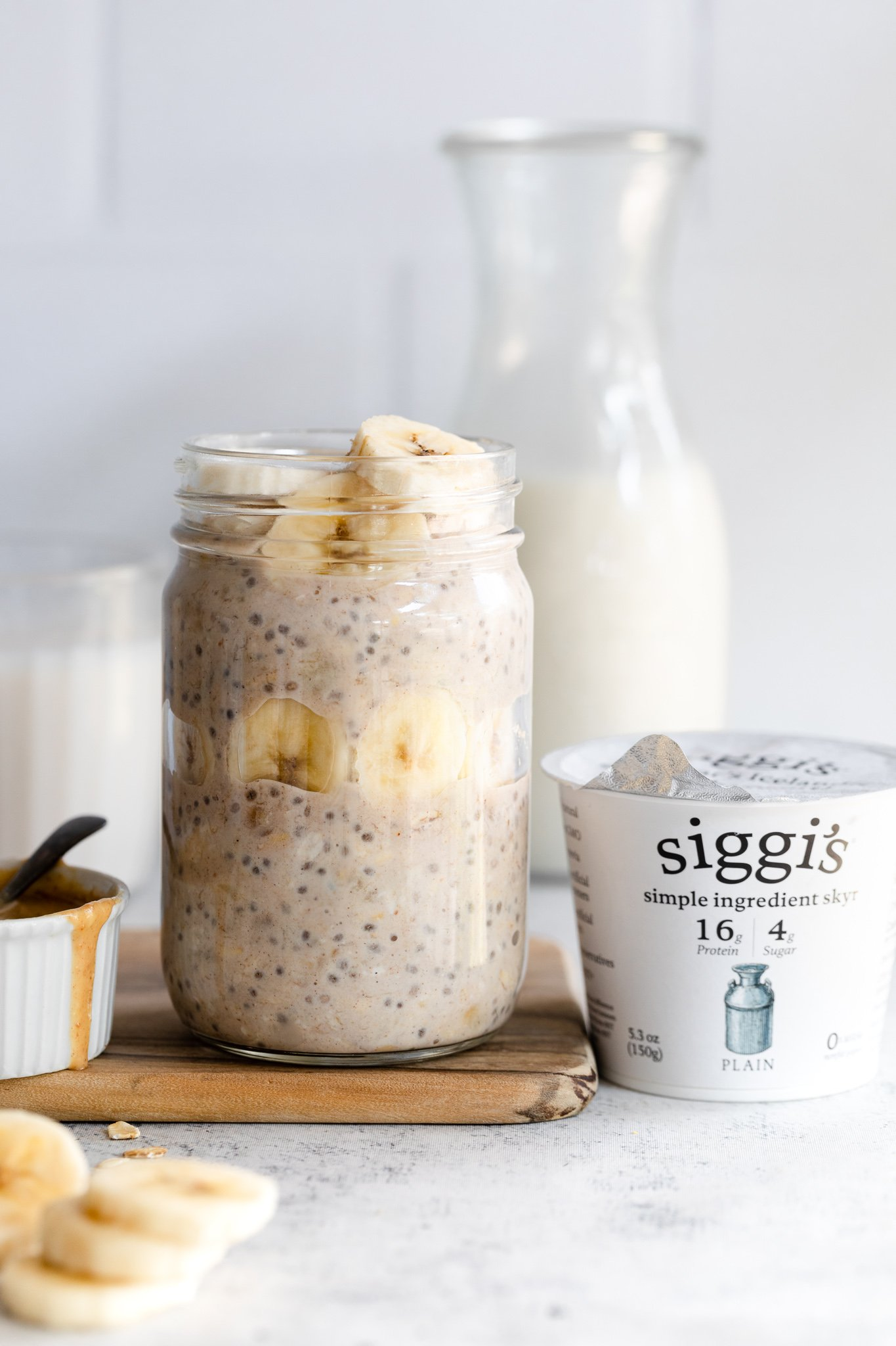 peanut butter banana overnight oats in a jar next to a container of yogurt