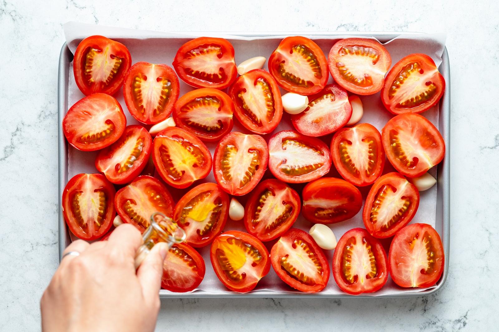 tomatoes and garlic on a baking sheet to make tomato sauce