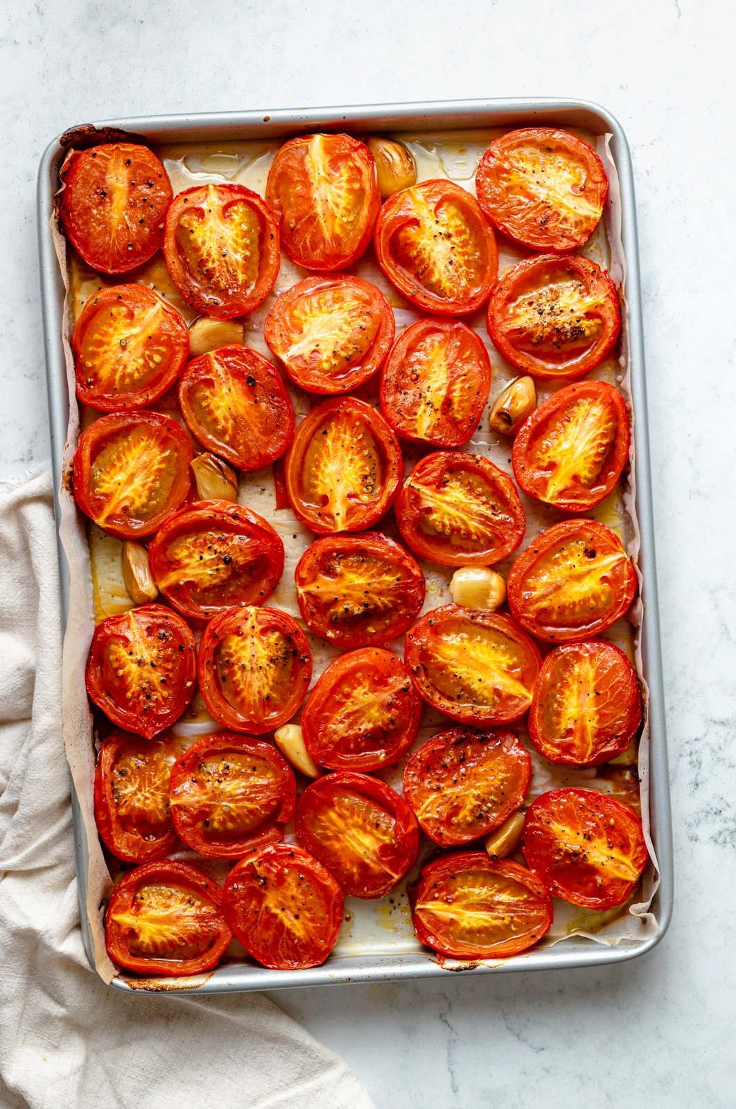 roasted tomatoes on a baking sheet to make homemade pasta sauce