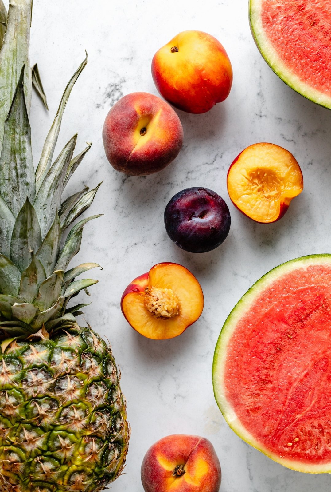pineapple, peaches, plums, nectarines and watermelon on a grey board