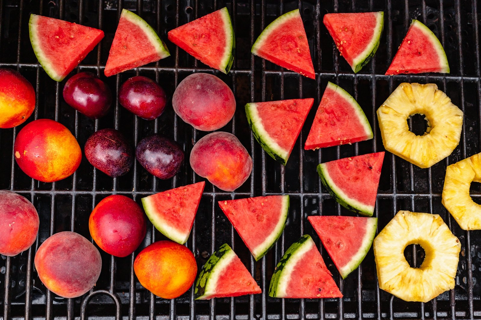 stone fruits, pineapple and watermelon on a grill