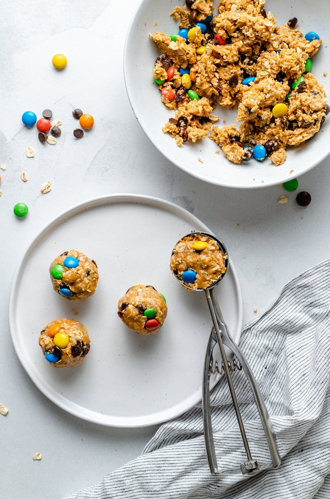 scooping monster cookie energy balls onto a plate