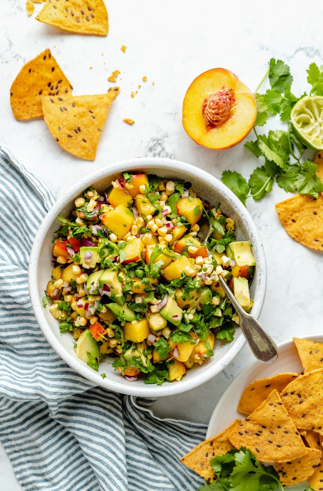 healthy avocado peach salsa in a bowl next to chips