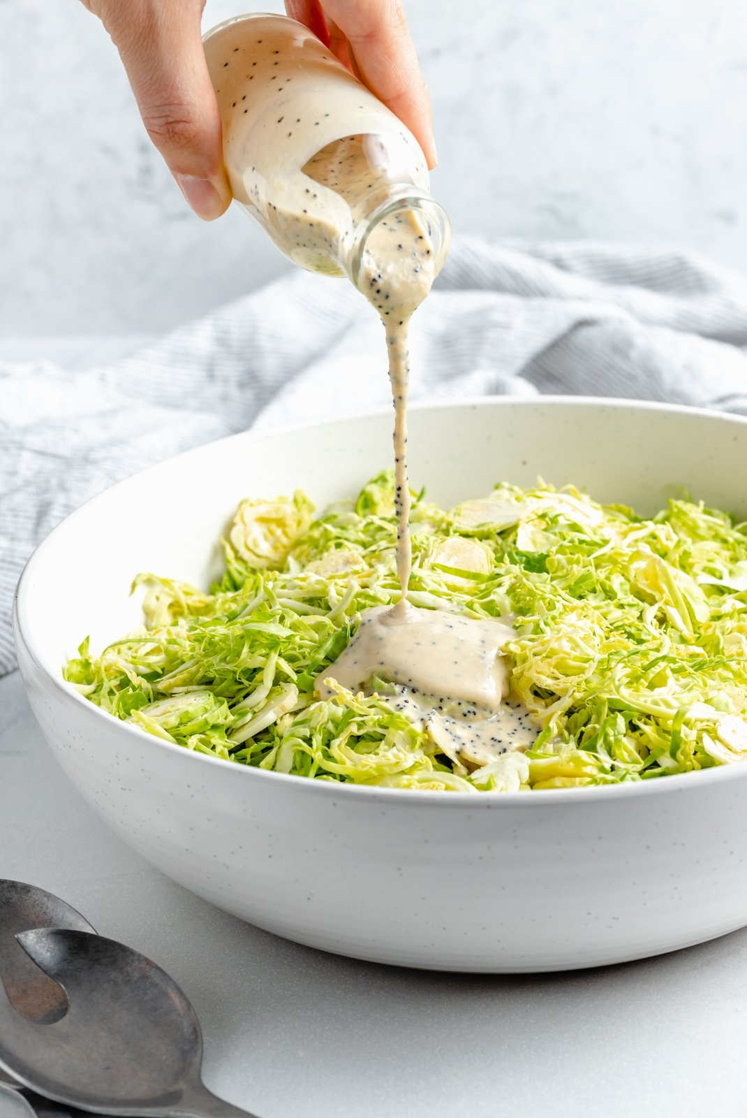 pouring tahini poppy seed dressing into a bowl of brussels sprouts