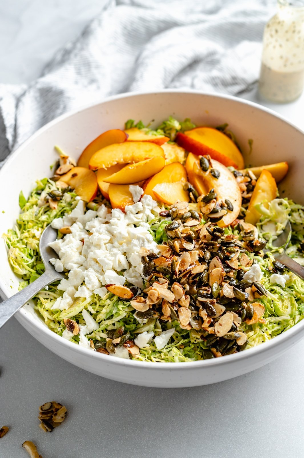 brussels sprouts peach salad with nuts and feta cheese in a bowl