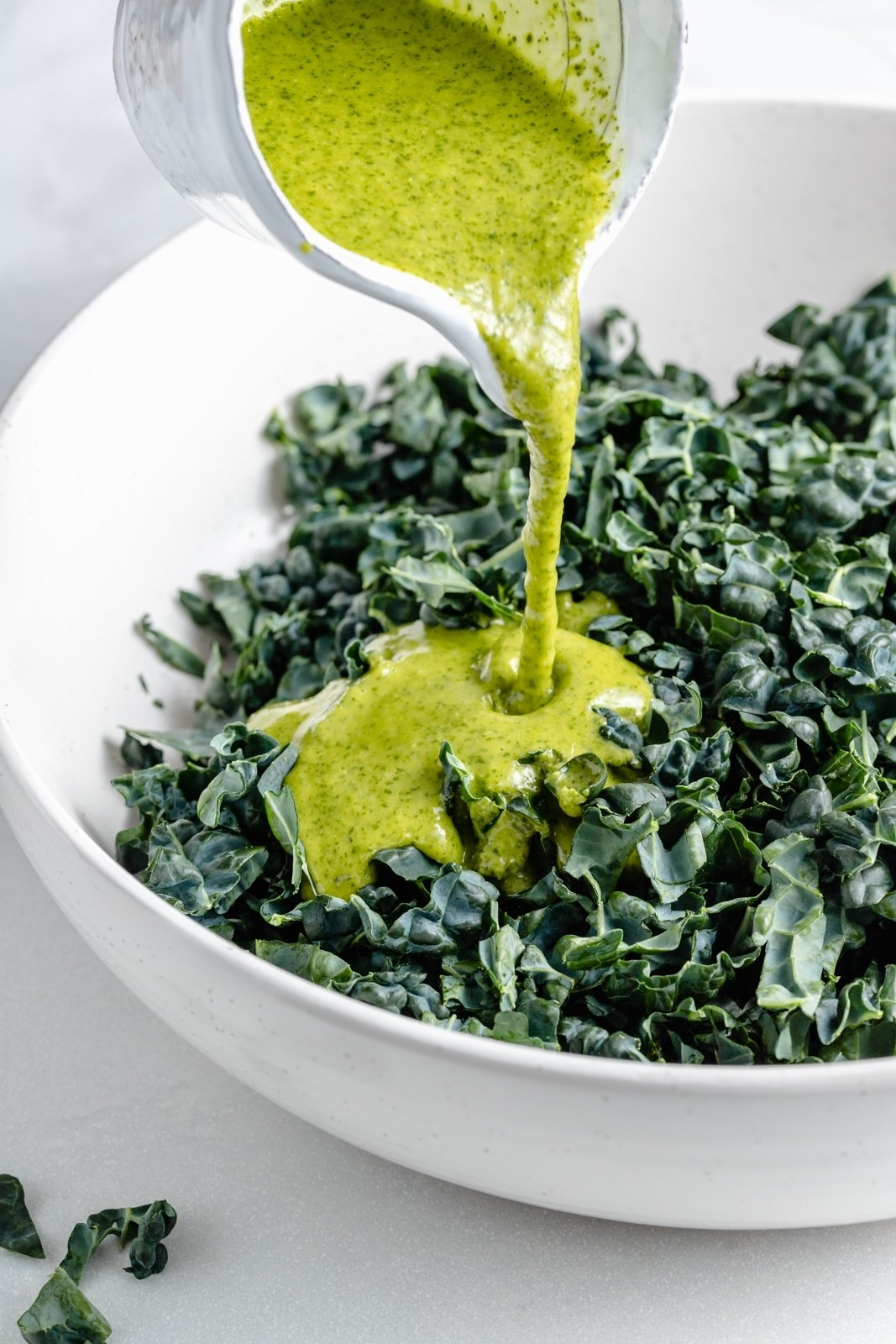 pouring cilantro lime dressing into a bowl of kale