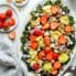 summer kale salad on a platter with strawberries and avocado