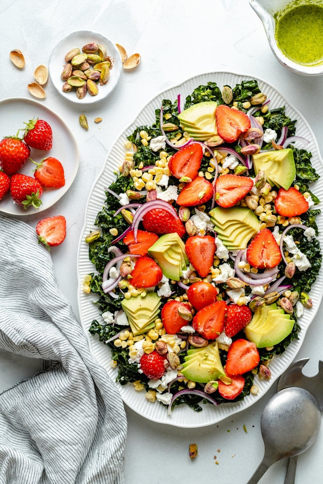 chopped kale salad with strawberries and avocado on a platter