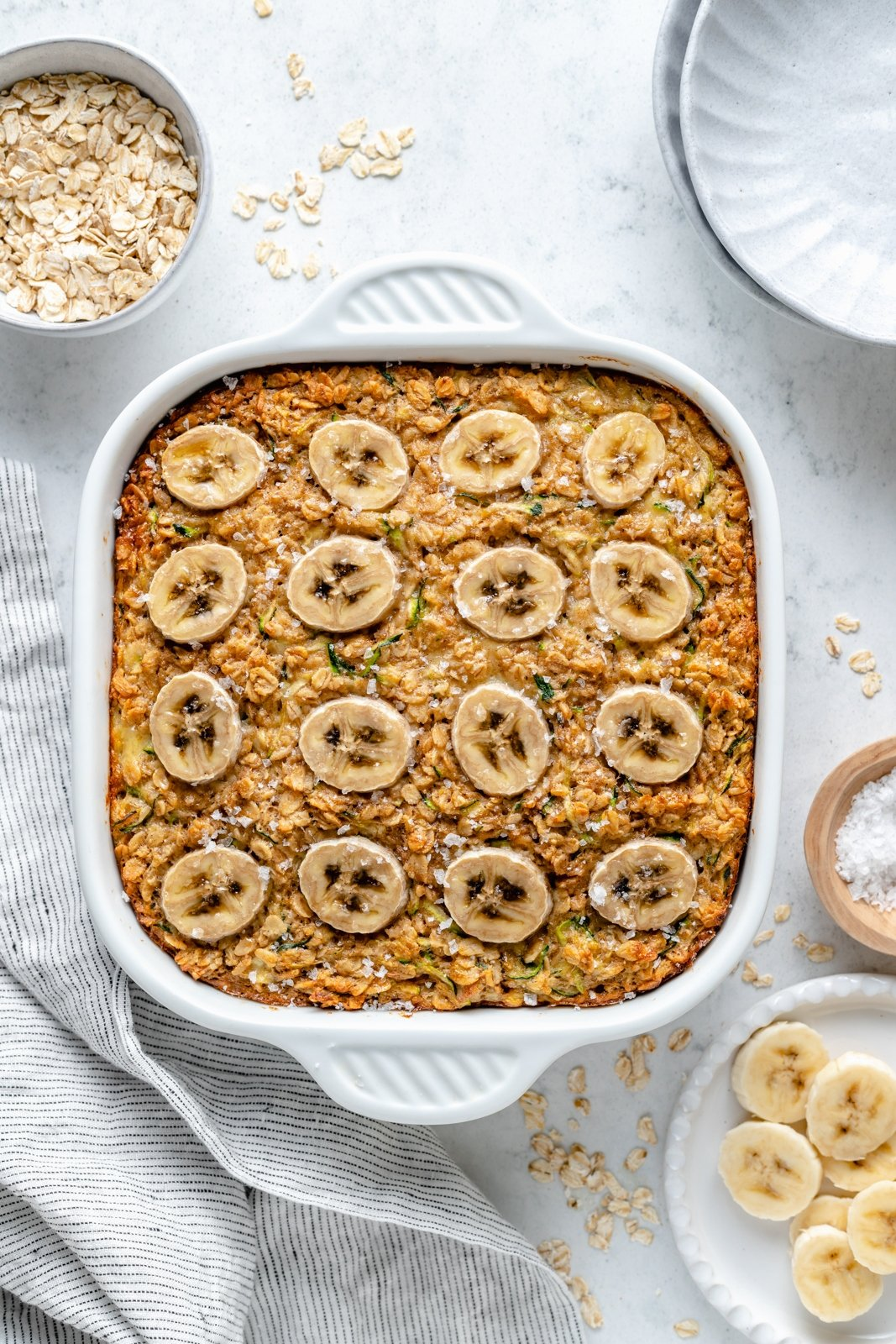banana zucchini baked oatmeal in a pan topped with banana slices