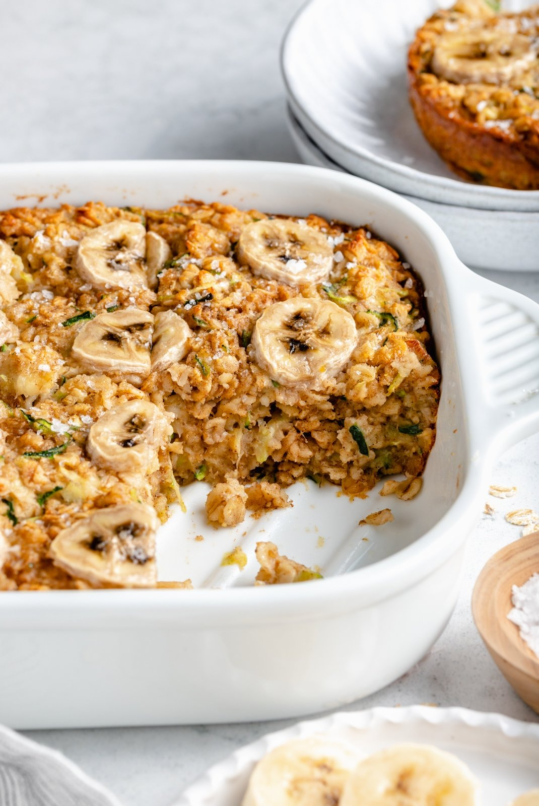 gluten free zucchini banana baked oatmeal in a pan with a sliced cut out