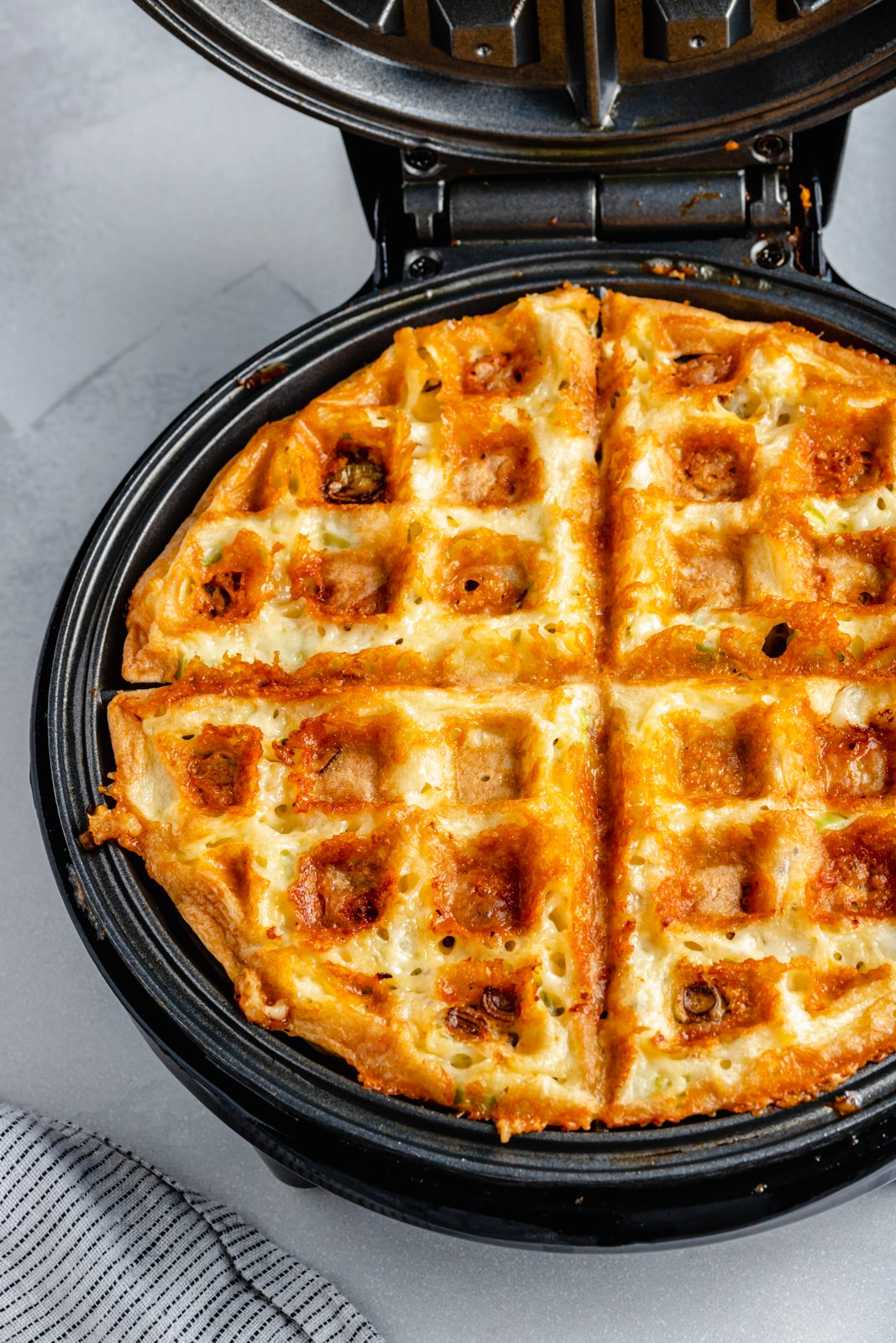 egg and cheese waffles in a waffle iron