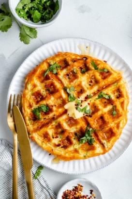 cheese and egg waffle on a plate with butter