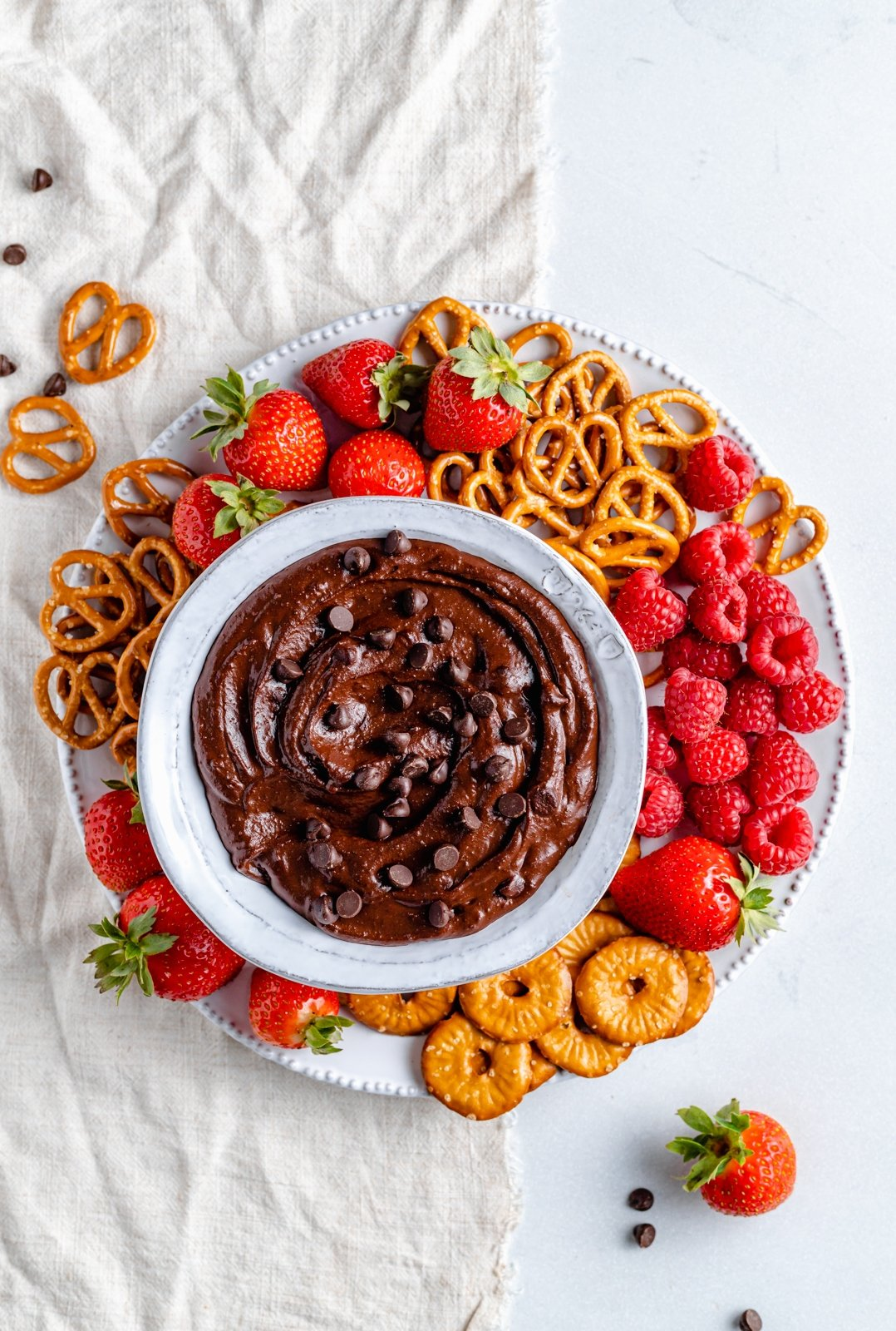 easy chocolate hummus in a bowl surrounded by berries and pretzels