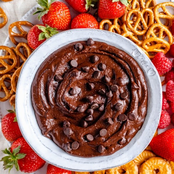 healthy chocolate hummus in a bowl surrounded by berries and pretzels