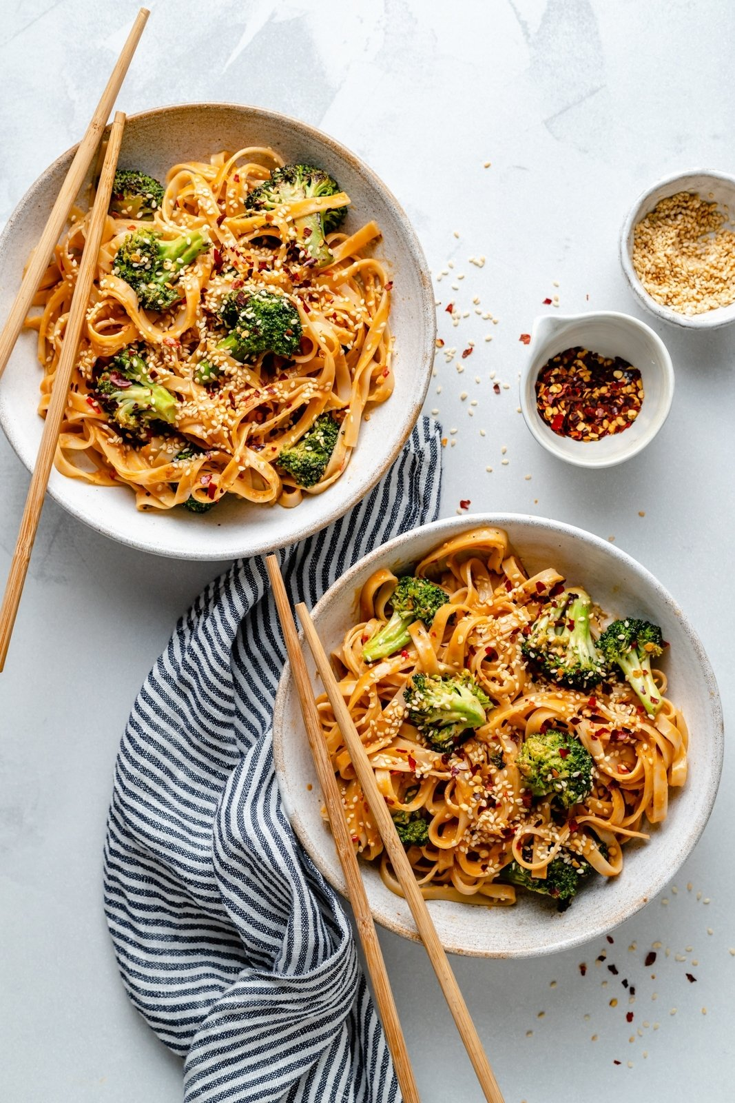 sesame tahini noodles with broccoli in two bowls