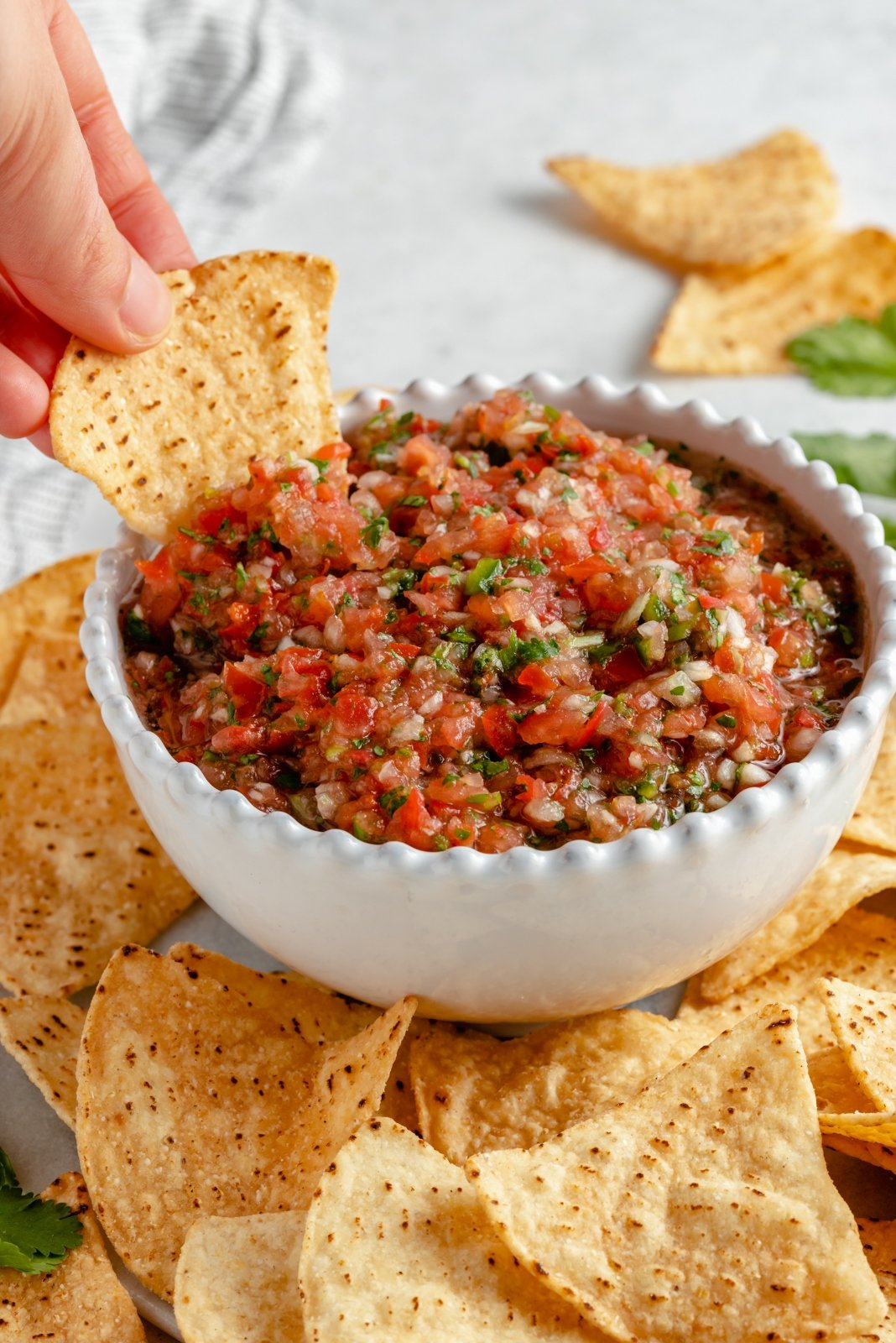 dipping a chip into homemade salsa