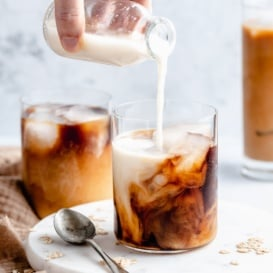 pouring homemade oat milk into a glass of iced coffee