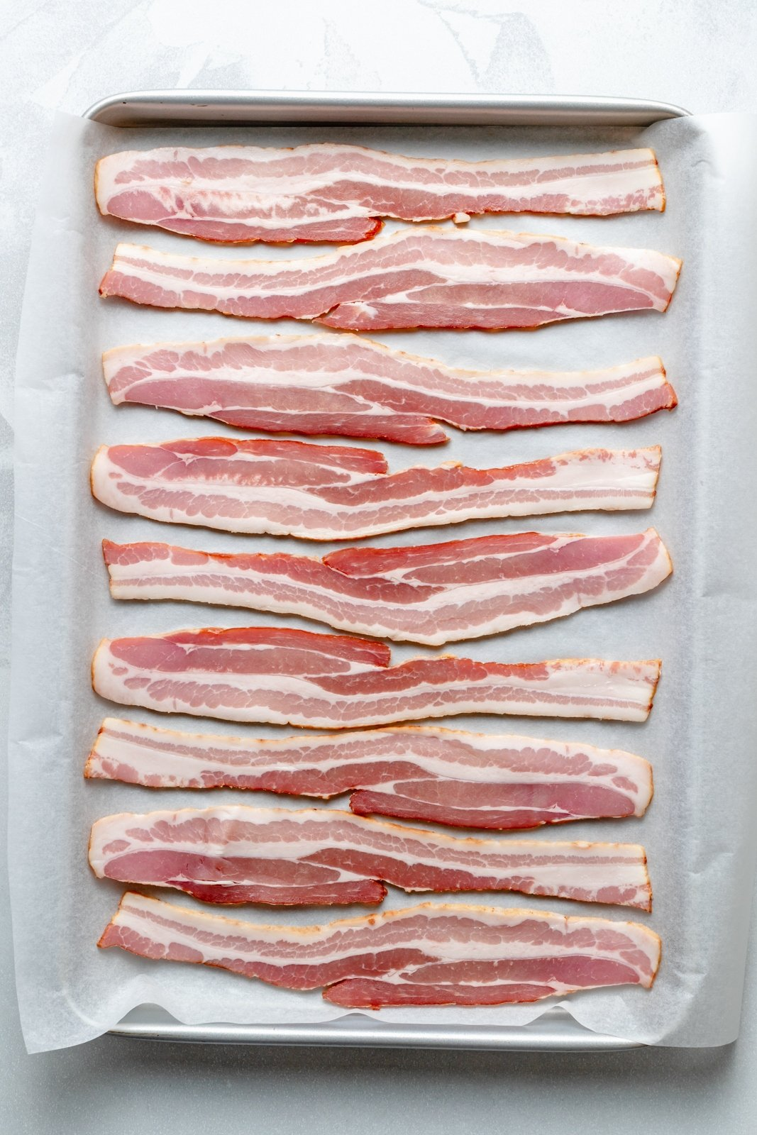 uncooked bacon on a baking sheet