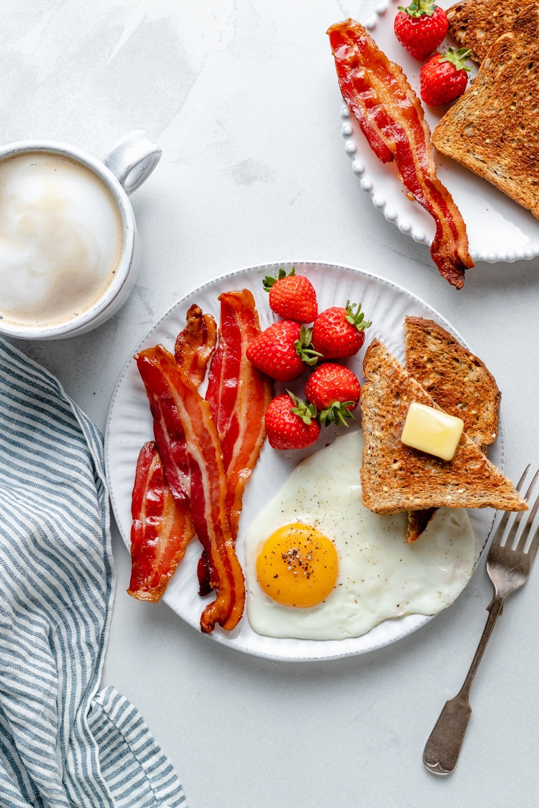 crispy bacon cooked in the oven on a plate with an egg, strawberries and toast