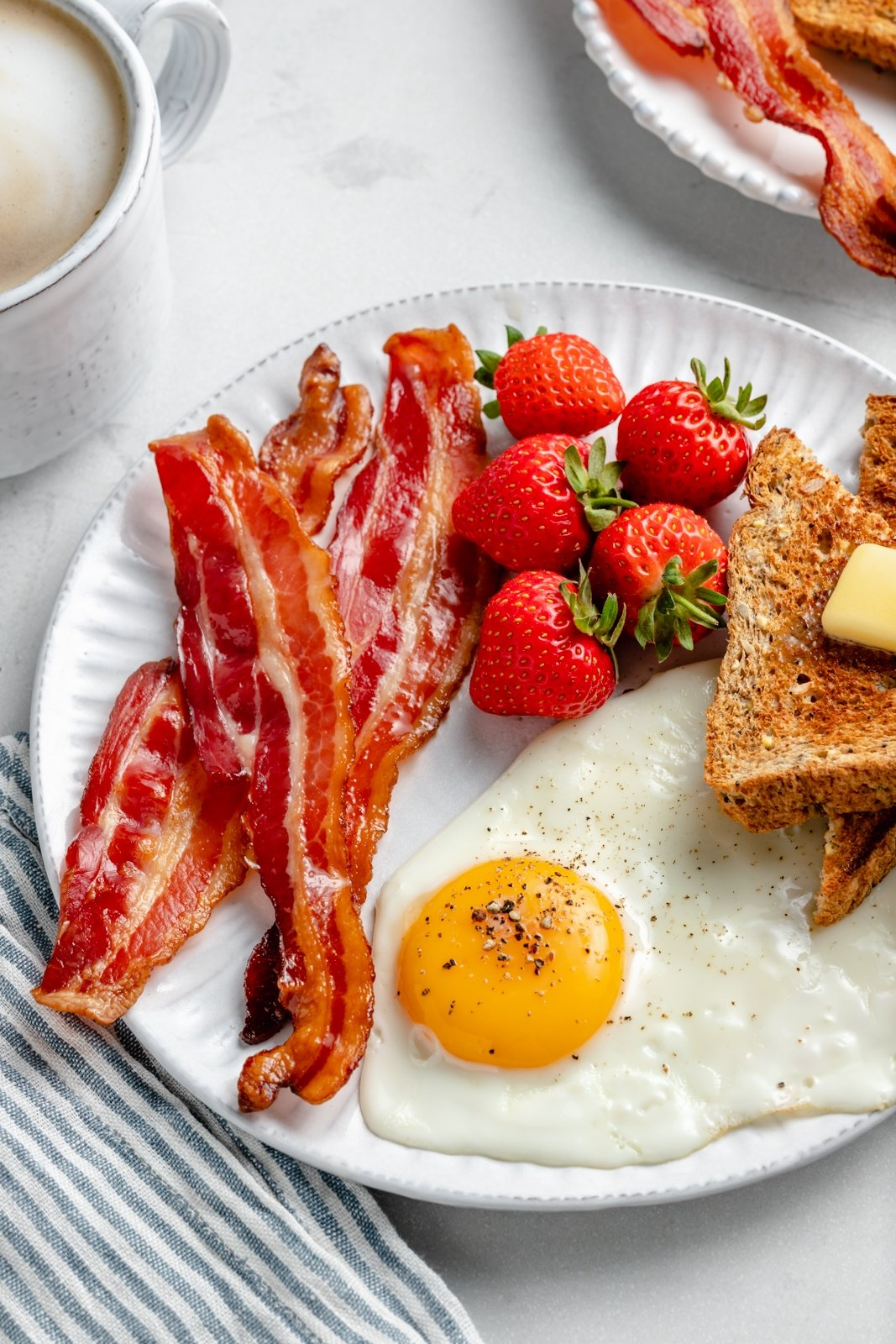 oven-baked bacon on a plate with an egg, strawberries and toast