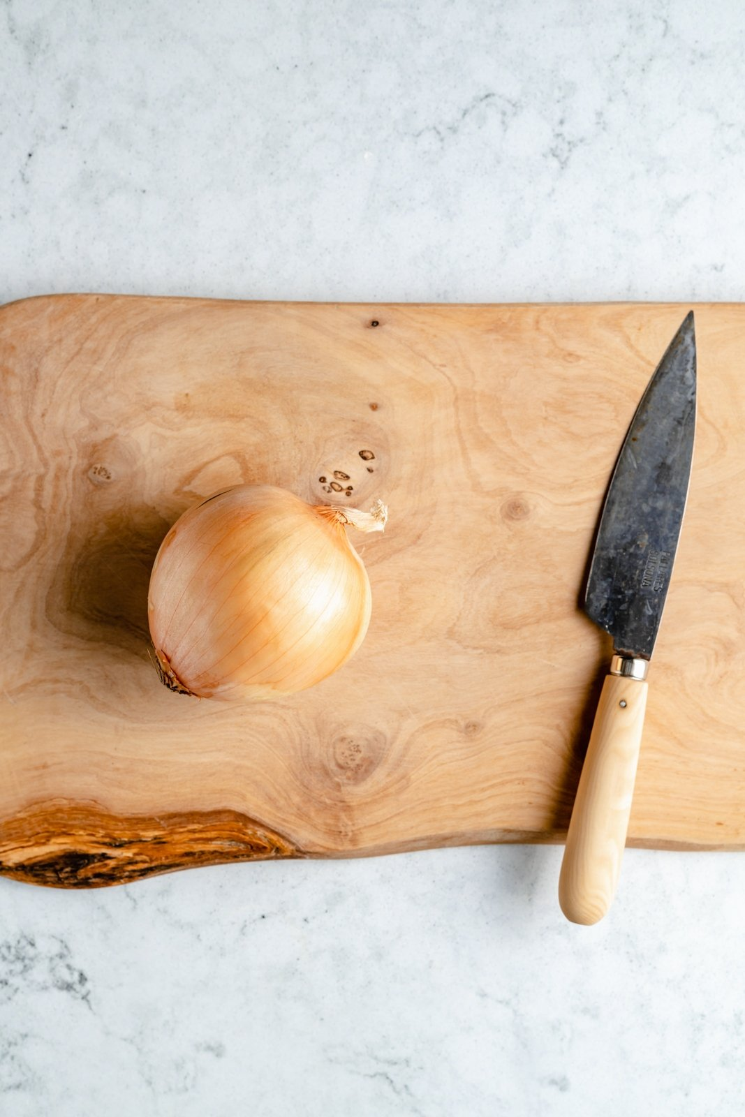 onion on a cutting board with a knife