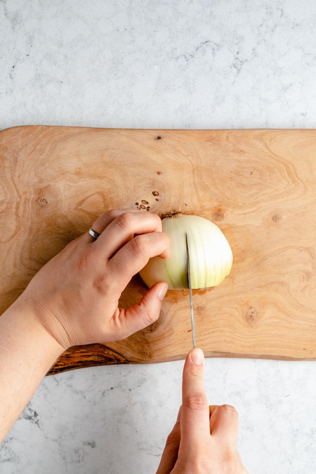cutting an onion on a cutting board