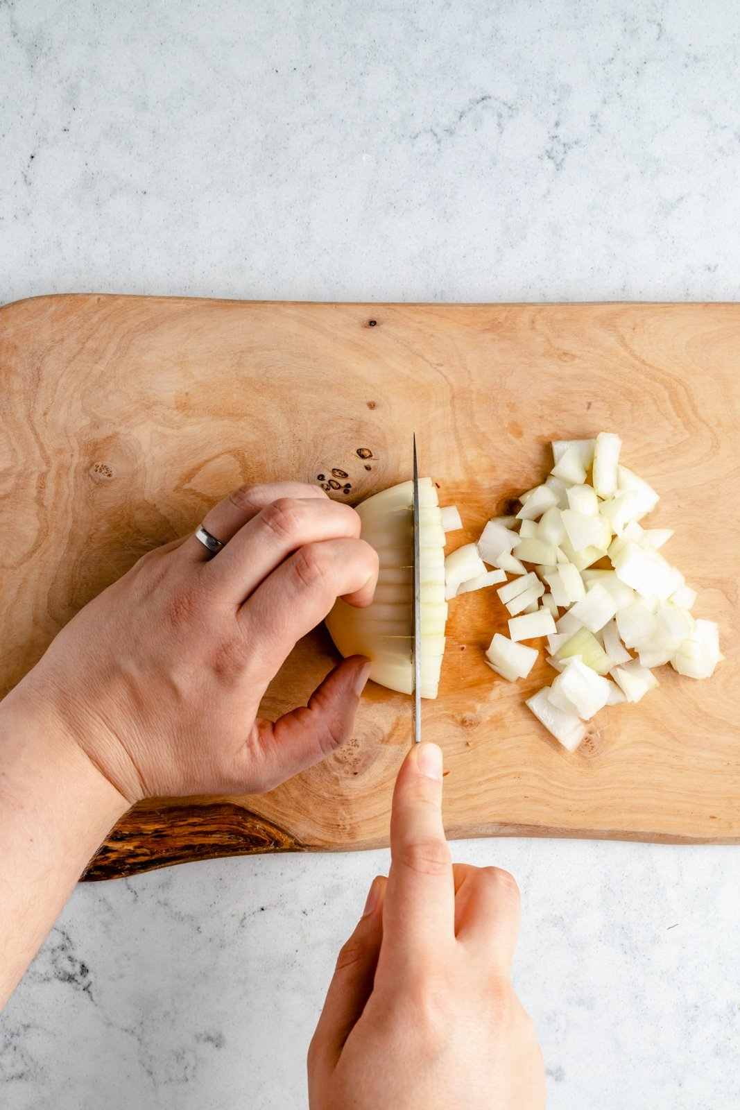 dicing an onion on a cutting board