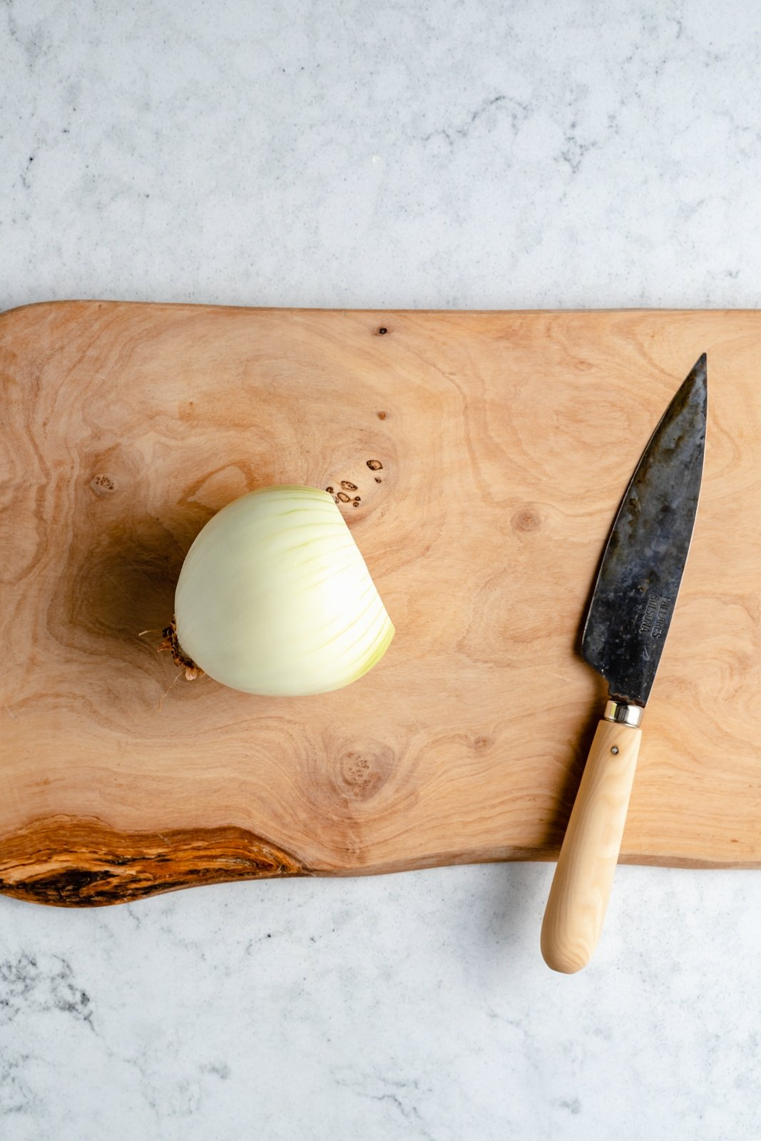 peeled onion on a cutting board with a knife