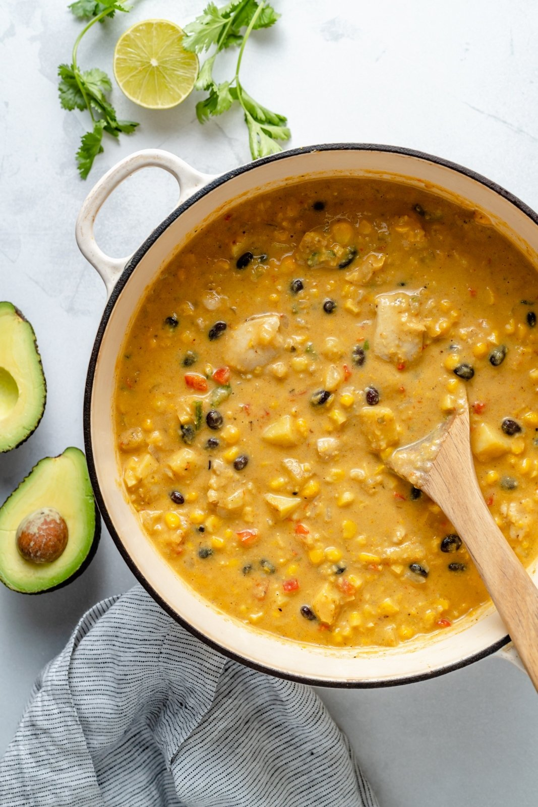 southwest corn chowder in a pot with a wooden spoon