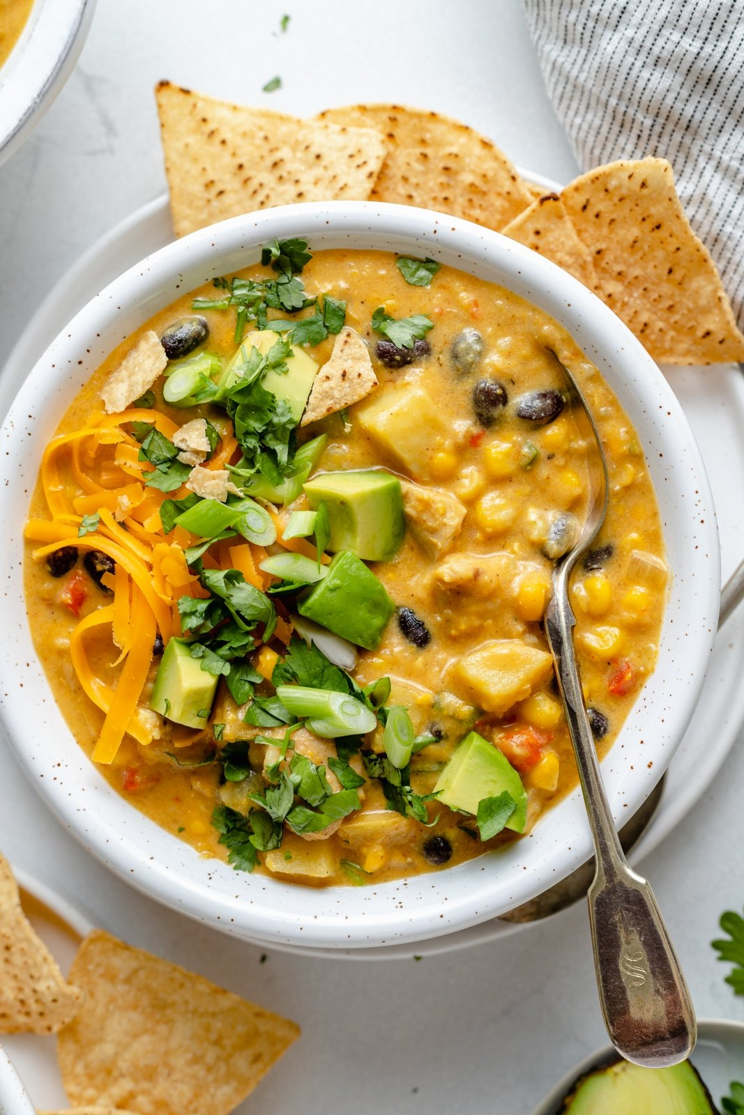 bowl of southwest chicken corn chowder topped with cilantro and avocado