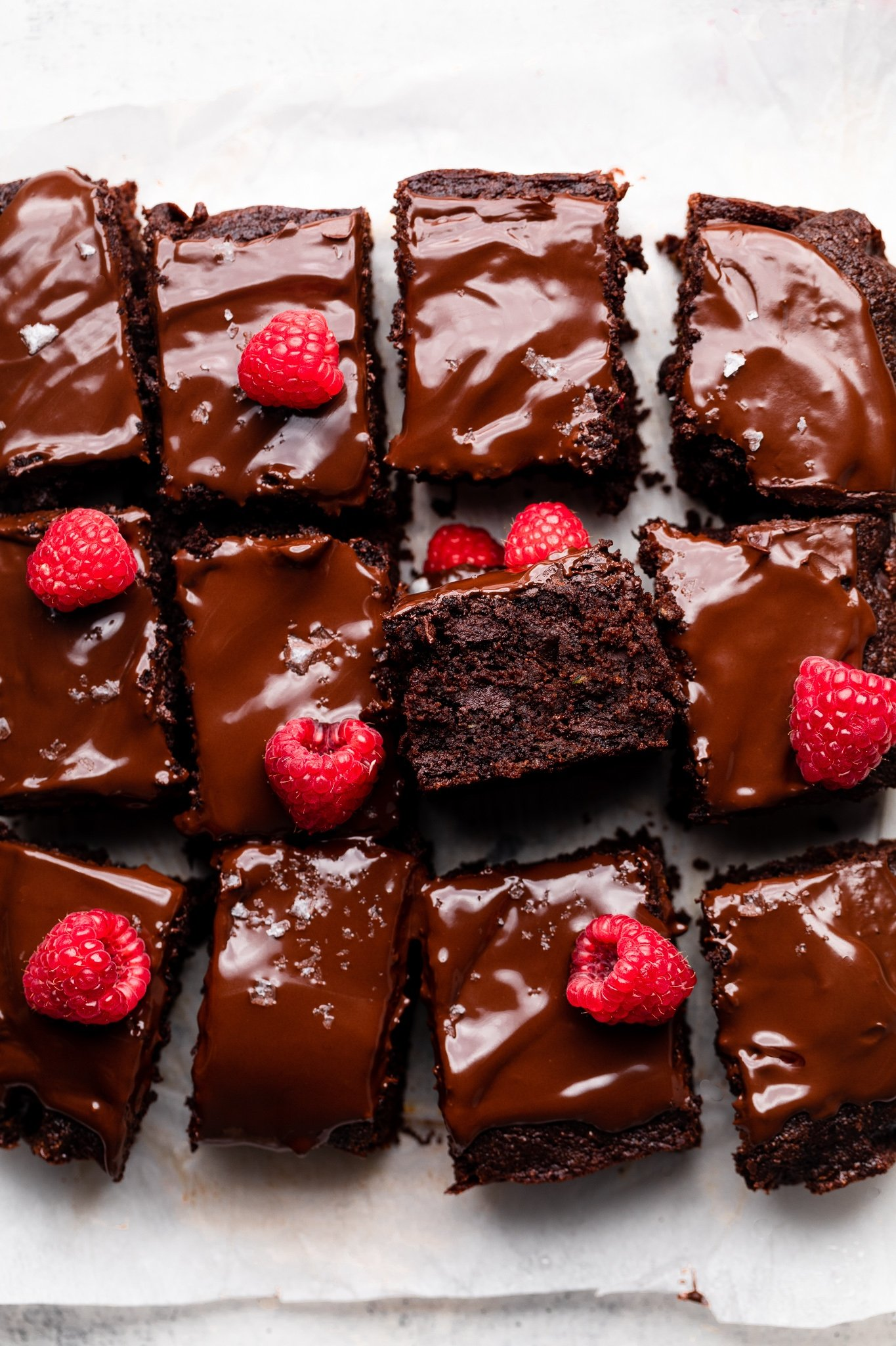 chocolate zucchini cake cut into squares and topped with raspberries