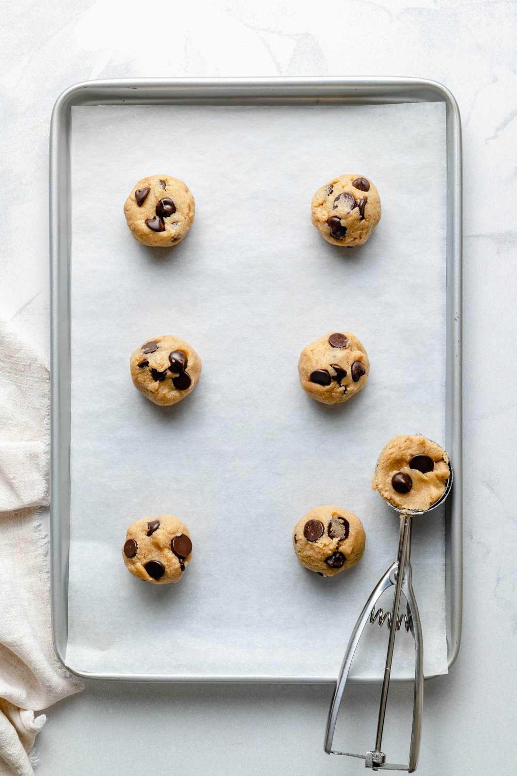 scooping grain free almond flour chocolate chip cookie dough onto a baking sheet