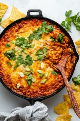 chicken enchilada dip in a skillet with a wooden spoon