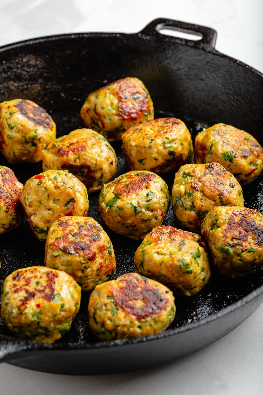 browning chicken meatballs in a skillet