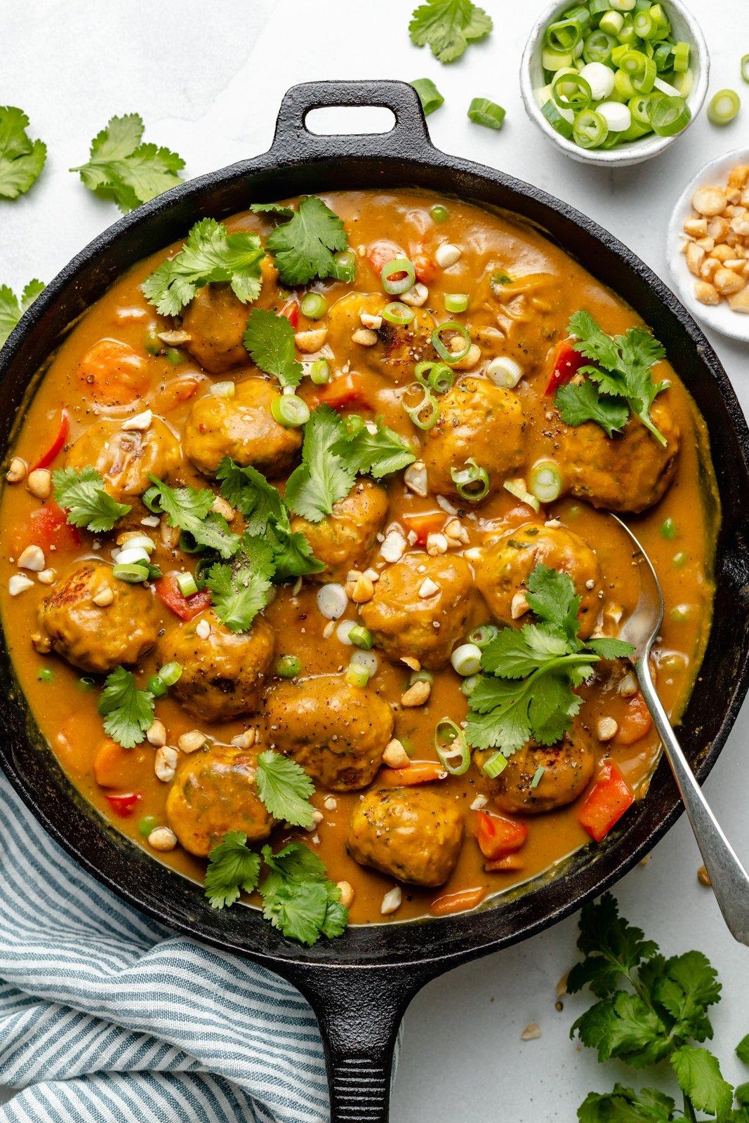 chicken meatballs in pumpkin curry sauce in a skillet