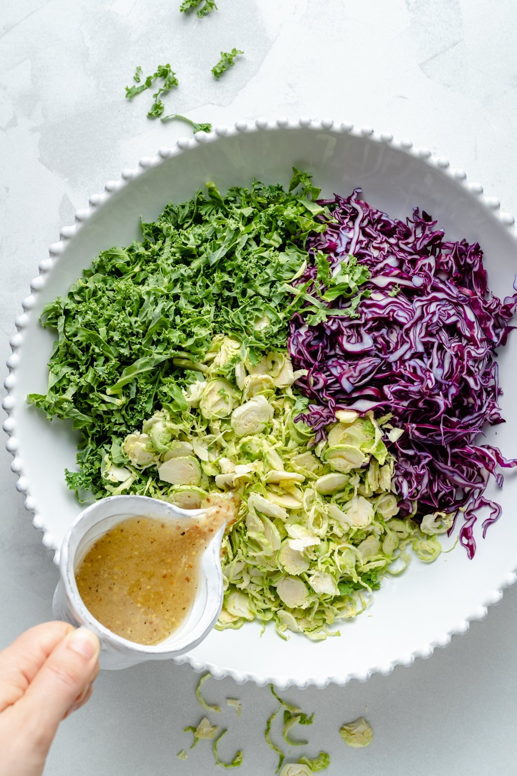pouring maple cider dressing into a bowl of brussels sprouts, kale and cabbage